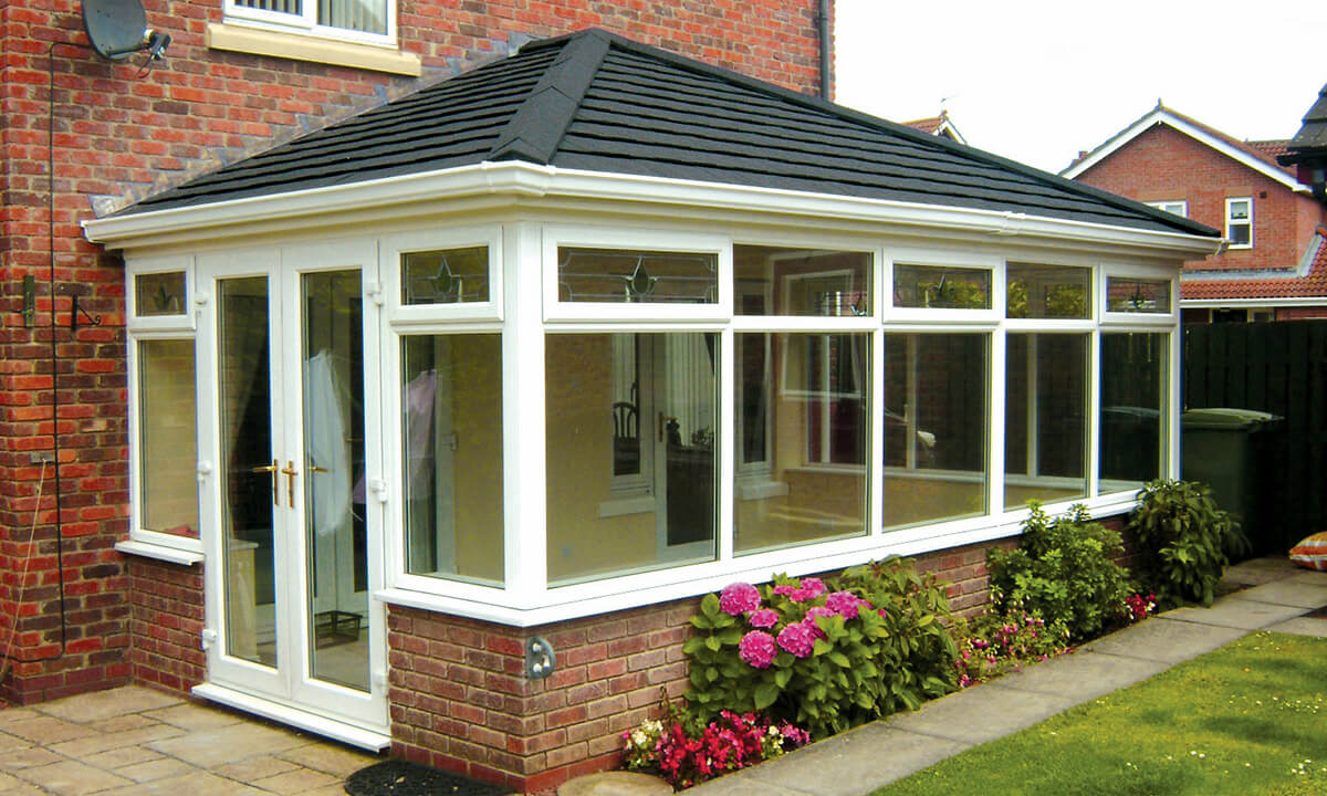 White uPVC conservatory with a black tiled roof