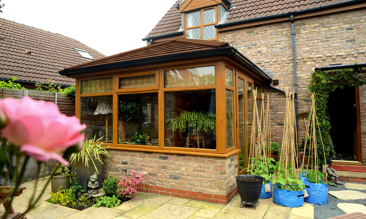 Golden oak effect uPVC conservatory with a tiled roof