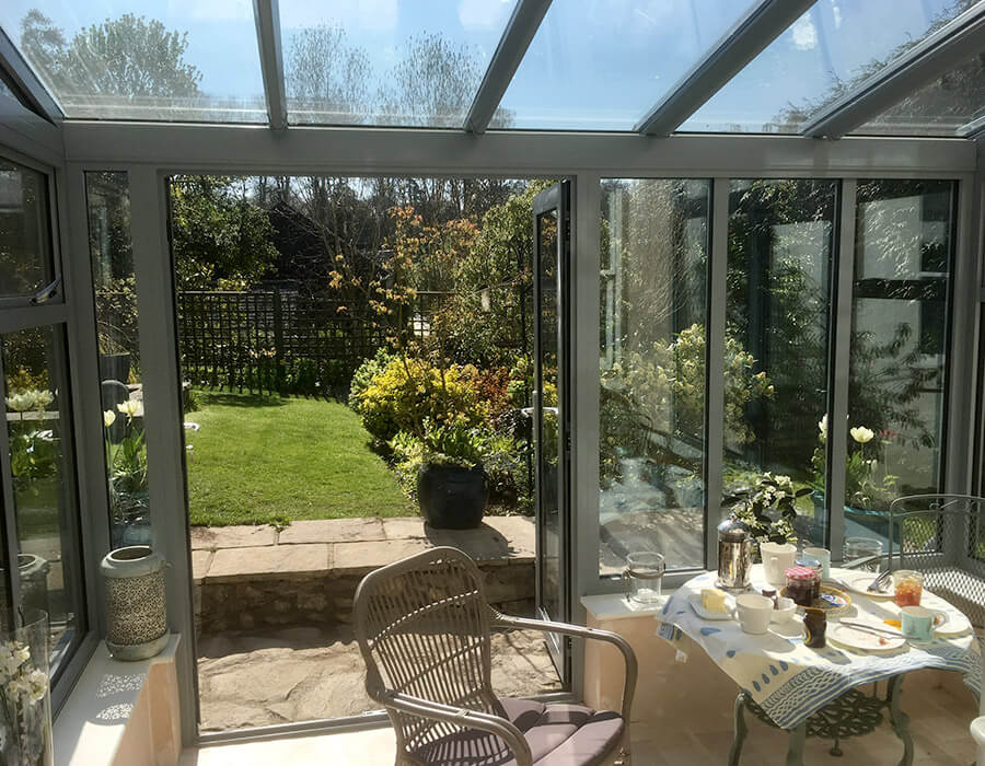 Grey uPVC lean to conservatory with a glass roof