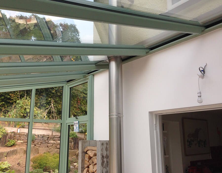 Green uPVC conservatory with glass roof interior view
