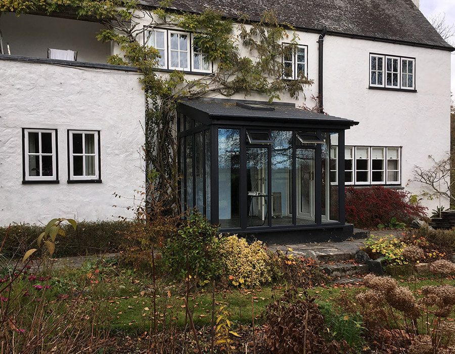 Black uPVC lean to conservatory with a tiled roof