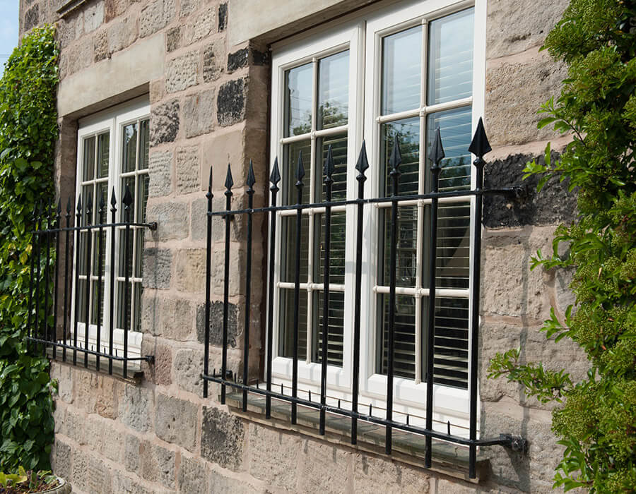 White uPVC casement windows with bars